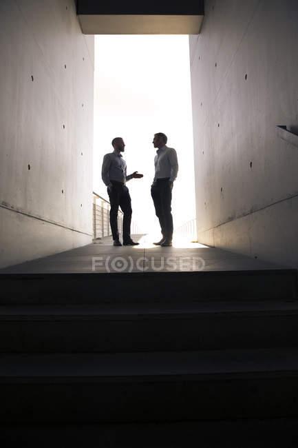 Silueta de dos hombres de negocios hablando en un pasillo - foto de stock