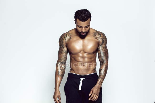 Татуйовані фізична спортсмен перед світлим фоном — Stock Photo