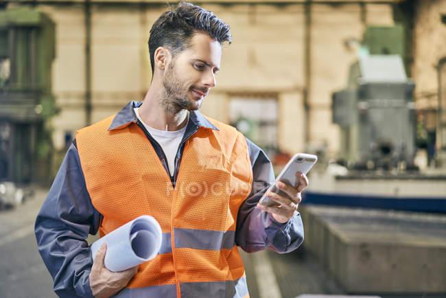 Улыбающийся человек с чертежом и глядя на мобильный телефон на заводе — стоковое фото