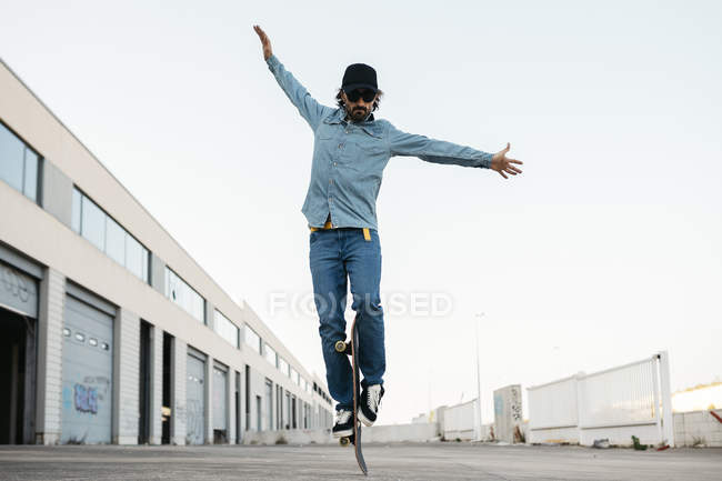 Trendy man in denim and cap skateboarding on street — Stock Photo