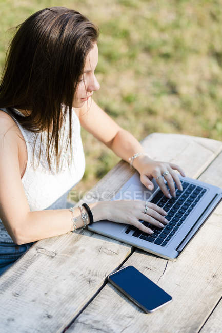 Giovane donna che utilizza il computer portatile su tavolo in legno all'aperto — Foto stock