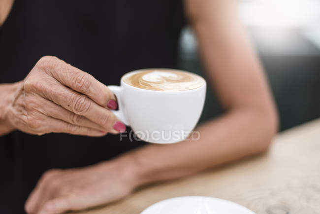 Close-up of senior woman holding a cup of cappuccino — Stock Photo