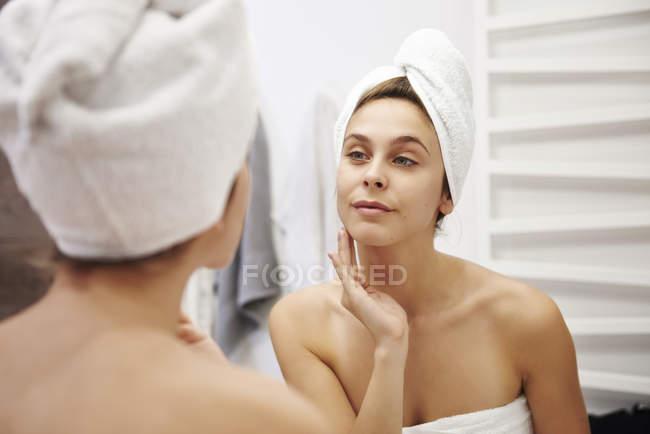 Зеркальное изображение молодой женщины, осматривающей лицо в ванной комнате — стоковое фото