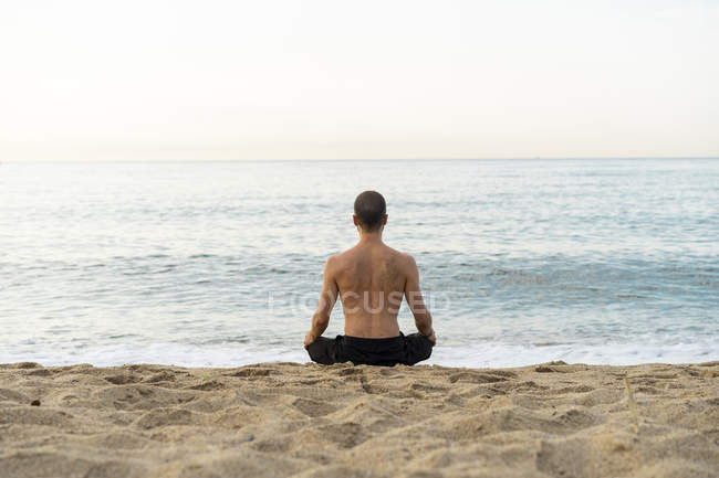 Spain. Man doing yoga on the beach in the evening, meditation, rear view — стоковое фото