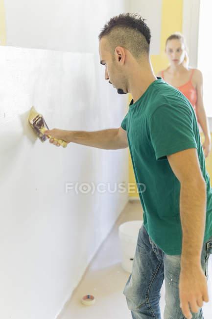Мужчина рисует стену в новом доме, пока его девушка смотрит — стоковое фото