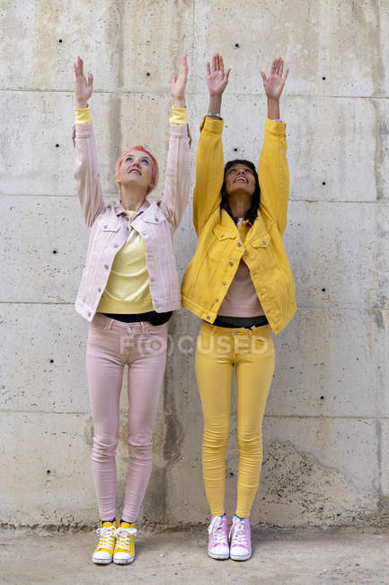 Two alternative friends wearing yellow and pink jeans clothes, posing, raising arms — Stock Photo