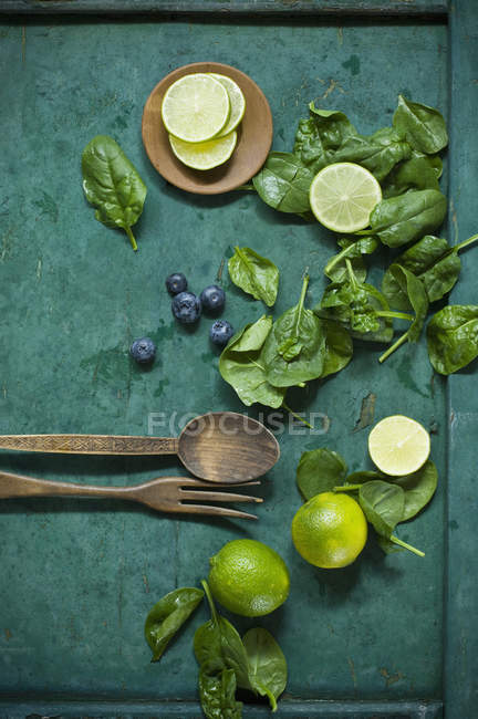 Salad ingredients and salad cutlery on green ground — Stock Photo