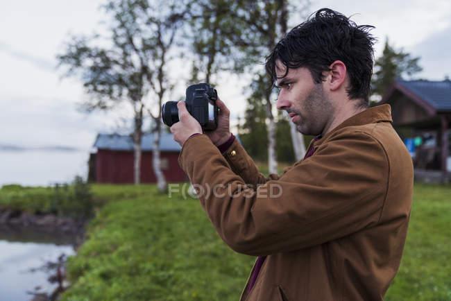 Sweden, Kiruna, Young man taking pictures of lake — Stock Photo