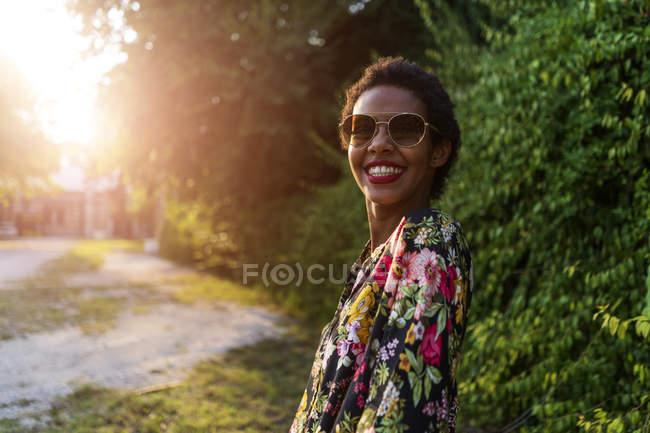 Портрет щасливого молодої жінки носіння сонцезахисні окуляри на відкритому повітрі на заході — стокове фото