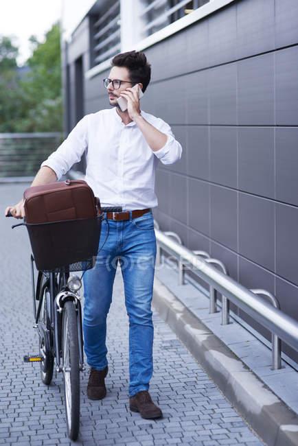 Homme d'affaires au téléphone poussant son vélo — Photo de stock