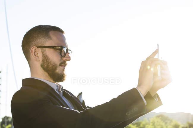 Бизнесмен, держащий планшет в подсветке на открытом воздухе — стоковое фото