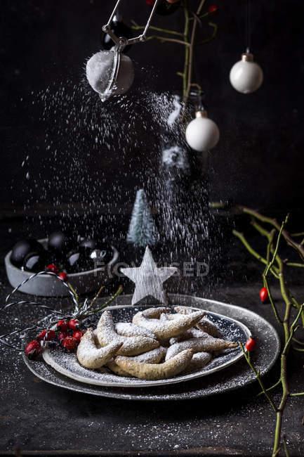 Saupoudrer les biscuits aux amandes avec le sucre glace — Photo de stock