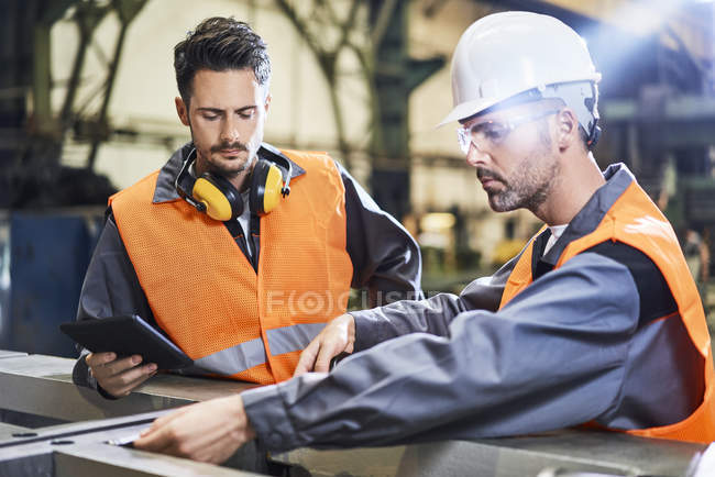 Men wearing protective workwear working in factory — Stock Photo