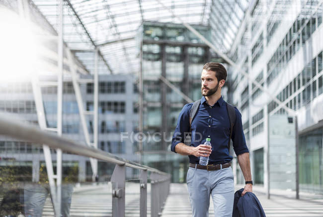 Молодий бізнесмен на ходу в будинку зі скляним фасадом — стокове фото