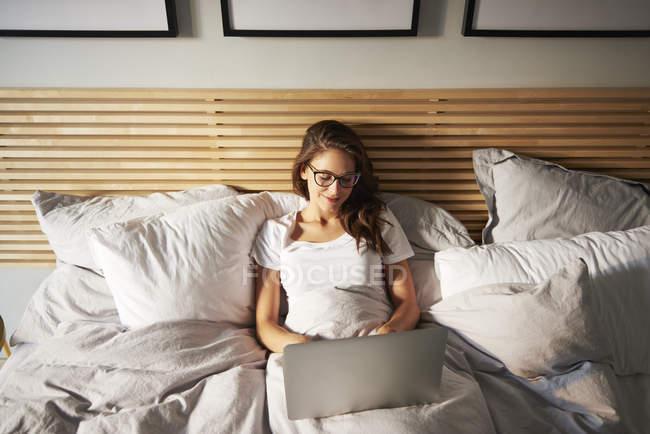 Portrait de jeune femme souriante couchée sur le lit à l'aide d'un ordinateur portable — Photo de stock