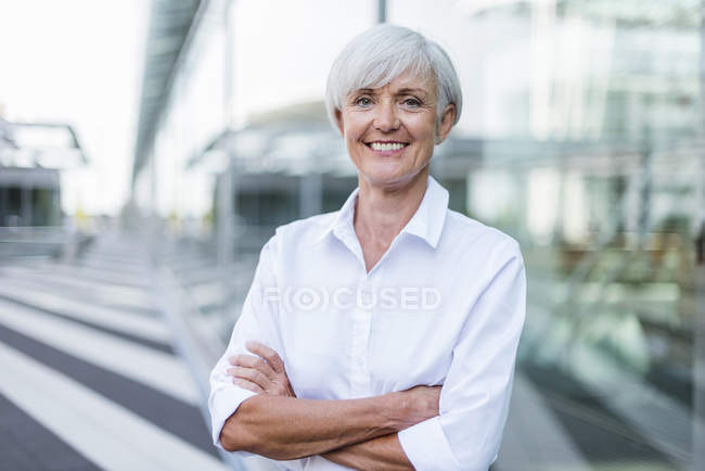 Portrait of smiling senior businesswoman standing in city — Stock Photo