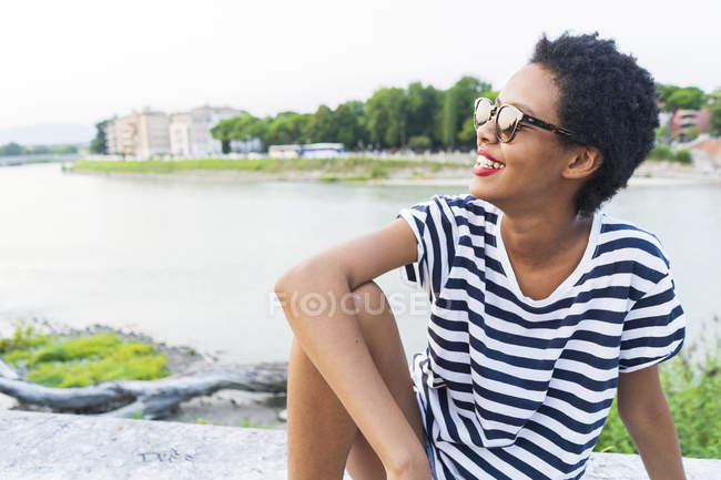 Smiling young woman wearing sunglasses sitting at riverside — Stock Photo