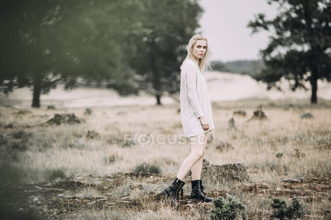 Young blond woman wearing boots and oversize pullover, full length — Stock Photo