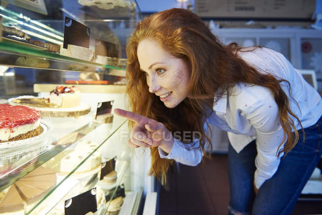 Woman choosing cake at cafe — Stock Photo