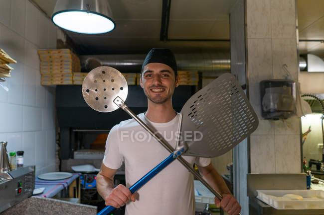 Портрет улыбающегося пекаря пиццы с кожурой пиццы и большим скиммером на кухне — стоковое фото