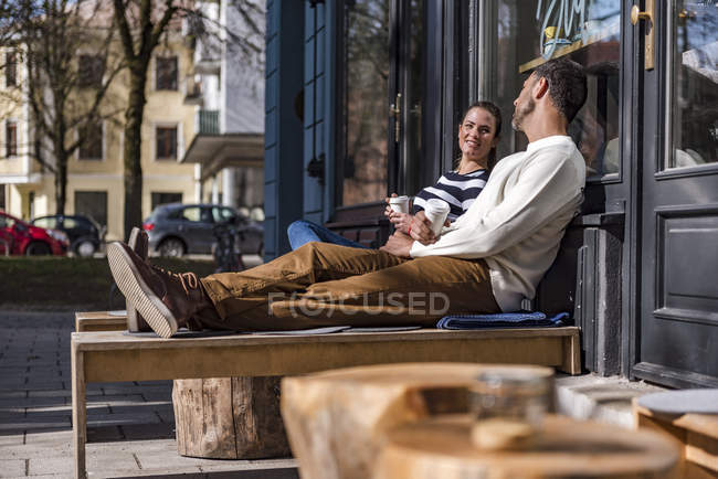 Man and woman sitting outside a cafe talking — Stock Photo