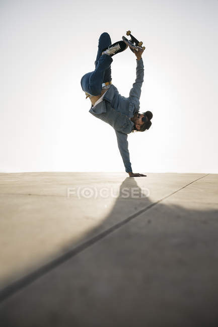 Stylish man in denim outfit showing trick with skate in handstand — Stock Photo