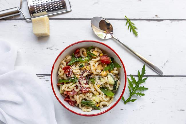 Bol de salade de nouilles avec maïs, concombre, tomates, roquette et parmesan râpé — Photo de stock