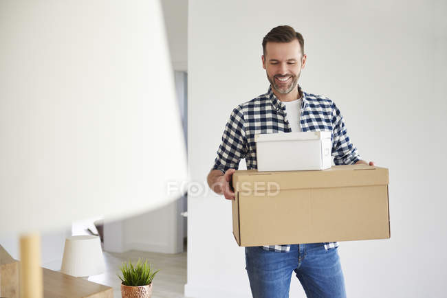 Happy man moving into new flat carrying cardboard box — Stock Photo