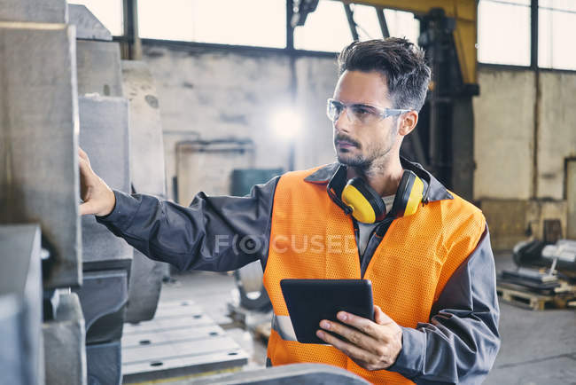Man with tablet wearing protective workwear working in factory — Stock Photo