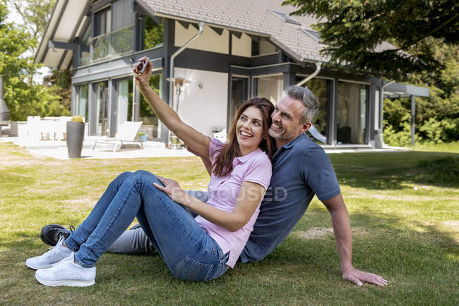 Happy couple sitting in garden of their home taking a selfie — Stock Photo