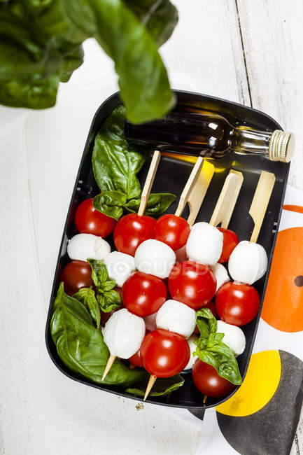 Lunch box of skewered cherry tomatoes and mozzarella cheese balls with basil leaves and vinaigrette — Stock Photo
