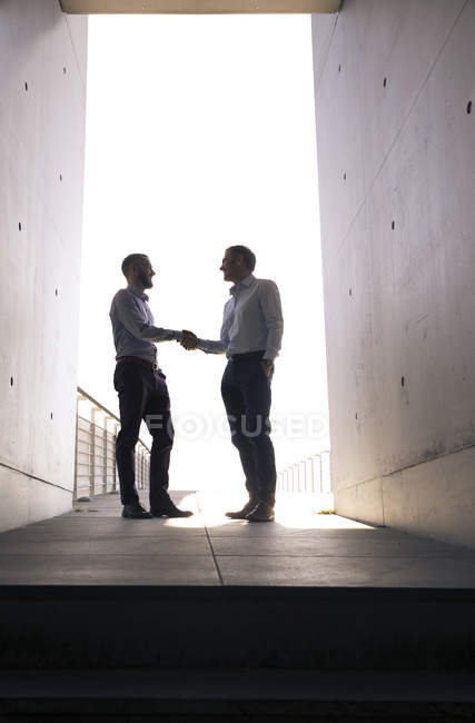 Two businessmen shaking hands in a passageway — Stock Photo