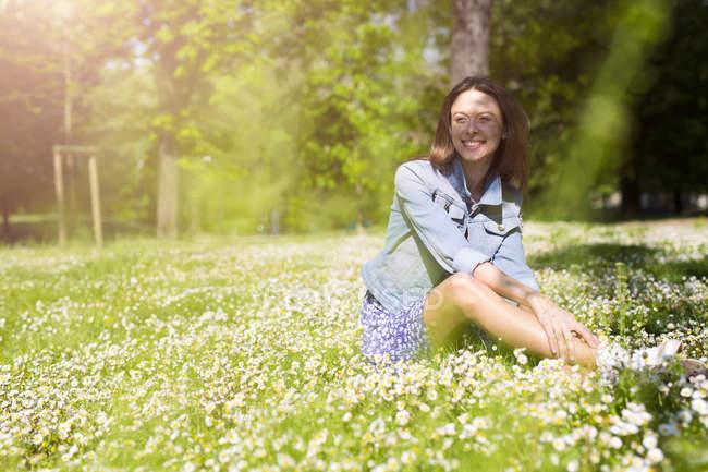 Sorridente giovane donna seduta nel parco — Foto stock