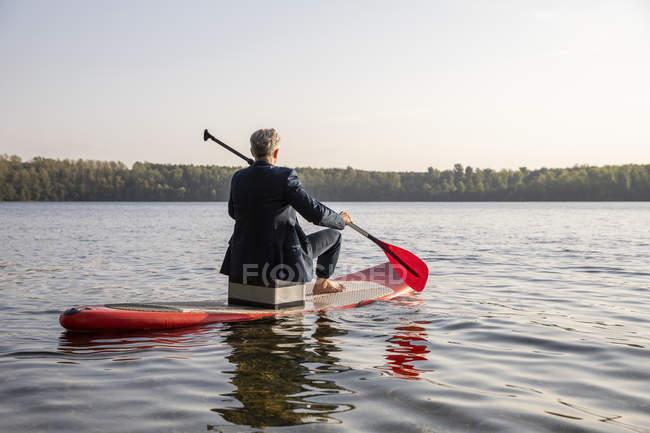 Rückansicht eines Geschäftsmannes, der auf dem See paddelt — Stockfoto