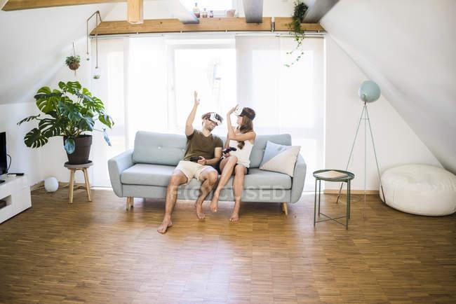 Glückliches Paar sitzt auf der Couch zu Hause mit vr Brille High Fiving — Stockfoto