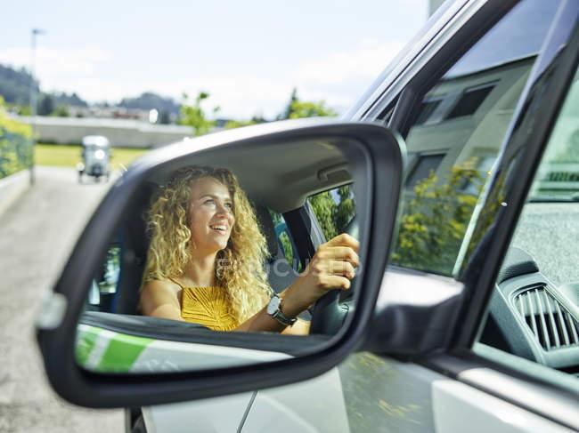 Réflexion dans le miroir d'aile de la femme de sourire conduisant la voiture électrique — Photo de stock