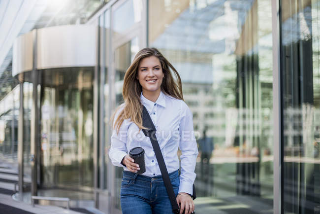 Smiling young businesswoman with bag and coffee to go — Stock Photo