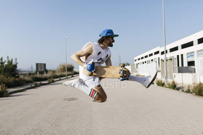 Sportive man jumping above ground with skateboard on hands — Stock Photo