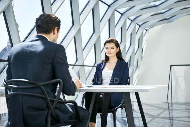 Businesswoman looking at businessman at desk in modern office — Stock Photo
