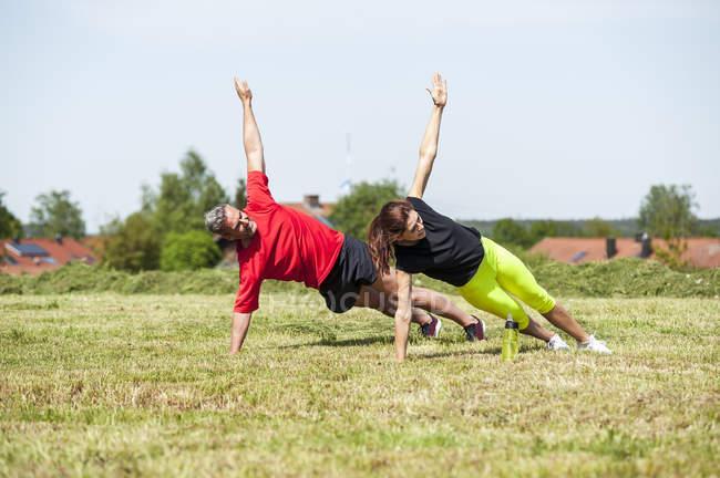 Casal fazendo exercício de prancha lateral no prado — Fotografia de Stock