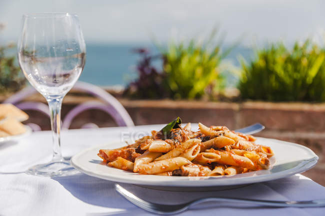 Italy, Atrani, plate of Penne Rigate with tomato sauce and tuna — Stock Photo