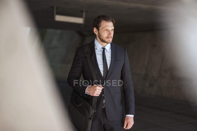 Confident businessman with laptop bag standing in underpass — Stock Photo