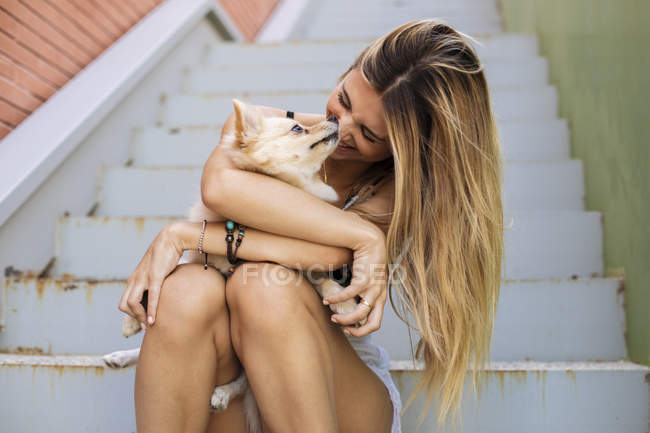 Souriant jeune femme assise sur les escaliers et tenant chien — Photo de stock