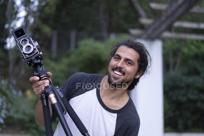 Портрет счастливого молодого человека с винтажной камерой — стоковое фото