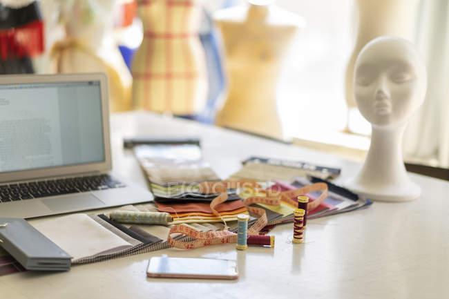 Artículos de costura en la mesa de trabajo en el estudio de un diseñador de moda - foto de stock