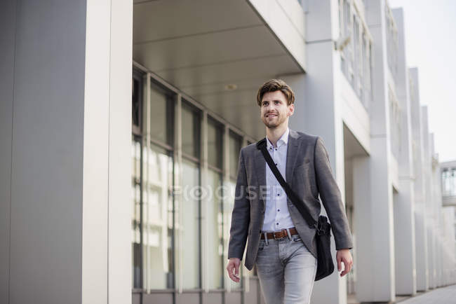 Smiling businessman with cross body bag in city on the move — Stock Photo