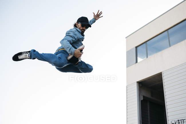 Homme à la mode dans le denim et la casquette faisant le saut dans la ville — Photo de stock