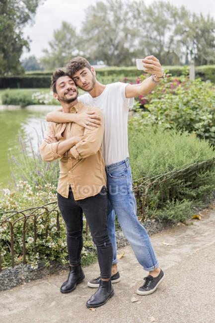 Портрет молодой пары геев, делающей селфи со смартфоном в городском парке — стоковое фото