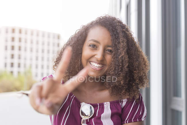 Positive african american looking at camera and gesturing peace sign with fingers — Stock Photo