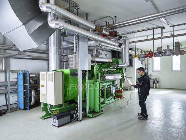 Usina combinada de calor e energia, trabalhador usando laptop na frente do motor a gás — Fotografia de Stock